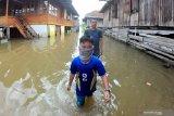 Warga menerobos banjir luapan Sungai Batanghari yang menggenangi permukiman di Kampung Tengah, Pelayangan, Jambi, Selasa (12/5/2020). Banjir luapan sungai terpanjang di Pulau Sumatera tersebut telah merendam kawasan permukiman di lima kabupaten/kota di Provinsi Jambi, meliputi Kabupaten Sarolangun, Batanghari, Muarojambi, Tanjungjabung Timur dan Kota Jambi. ANTARA FOTO/Wahdi Septiawan/wsj.