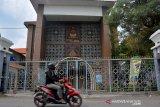 Warga melintas di depan pintu masuk makam Gus Dur di Pondok Pesantren Tebuireng, Kecamatan Cukir, Kabupaten Jombang, Jawa Timur, Selasa (19/5/2020). Kawasan wisata religi ziarah makam Presiden keempat KH Abdurrahman Wahid atau Gus Dur di Ponpes Tebuireng yang biasanya ramai dikunjungi peziarah saat bulan Ramadhan ditutup sejak 16 Maret hingga batas waktu yang belum ditentukan akibat pandemi virus Corona. Antara Jatim/Syaiful Arif/zk.