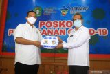 Ketua KADIN Kalbar sekaligus KNPI Kalbar Joni Isnaini (kiri) secara simbolis menyerahkan bantuan Alat Pelindung Diri (APD) kepada Kepala Dinas Kesehatan Provinsi Kalbar dr Harisson (kanan) di Posko Penanganan COVID-19 Kalbar di Pontianak, Rabu (20/5/2020). Kamar Dagang dan Industri Indonesia (KADIN) Kalbar bersama Komite Nasional Pemuda Indonesia (KNPI) Kalbar menyerahkan bantuan berupa seratus alat pelindung diri (APD) untuk para tenaga medis yang sedang berjuang mengatasi pandemik COVID-19 di daerah setempat. ANTARA FOTO/Jessica Helena WuysangJESSICA HELENA WUYSANG/JESSICA HELENA WUYSANG (JESSICA HELENA WUYSANG/JESSICA HELENA WUYSANG)