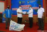 Ketua KADIN Kalbar sekaligus KNPI Kalbar Joni Isnaini (ke dua kiri) secara simbolis menyerahkan bantuan Alat Pelindung Diri (APD) kepada Kepala Dinas Kesehatan Provinsi Kalbar dr Harisson (ke dua kanan) di Posko Penanganan COVID-19 Kalbar di Pontianak, Rabu (20/5/2020). Kamar Dagang dan Industri Indonesia (KADIN) Kalbar bersama Komite Nasional Pemuda Indonesia (KNPI) Kalbar menyerahkan bantuan berupa seratus alat pelindung diri (APD) untuk para tenaga medis yang sedang berjuang mengatasi pandemik COVID-19 di daerah setempat. ANTARA FOTO/Jessica Helena Wuysang