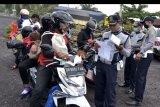 Petugas memeriksa surat jalan pengendara di Tabanan, Bali, Kamis (21/5/2020). Pemeriksaan yang dilakukan di jalur menuju Pelabuhan Gilimanuk tersebut dilakukan untuk mengantisipasi warga yang akan melakukan perjalanan mudik menuju Pulau Jawa sebagai salah satu upaya pencegahan penyebaran COVID-19. ANTARA FOTO/Fikri Yusuf/nym