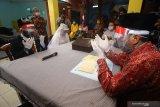 Pasangan pengantin Yoga Prianatha (kiri) dan Ika Wahyuning Sejati (kedua kiri) mengikuti rangkaian prosesi akad nikah di Kantor Urusan Agama (KUA) Tandes, Surabaya, Jawa Timur, Kamis (21/5/2020). Pemerintah melalui Kementerian Agama mengizinkan diselenggarakannya prosesi akad nikah di tengah pandemi COVID-19 dengan syarat mematuhi protokol kesehatan di antaranya dihadiri tidak lebih dari 10 orang, menggunakan masker serta menjaga jarak fisik guna mencegah penyebaran virus corona. Antara Jatim/Moch Asim/zk.