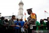 Kasat Lantas Polresta Banda Aceh AKP Yasnil Akbar Nasution SIK bersama anggota Ikatan Fisioterapi Indonesia (IFI) menyerahkan masker kepada warga yang melintas di depan Masjid Raya Baiturrahman, Banda Aceh, Aceh, Kamis (21/5/2020). Pembagian 1.000 lebih masker dan paket makanan berbuka puasa dari IFI cabang Banda Aceh sebagai wujud dukungan terhadap peraturan wajib memakai pelindung wajah guna mengantisipasi penularan serta penyebaran COVID-19. Antara Aceh/Irwansyah Putra.