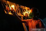 Seorang anak menyalakan lampu minyak yang diletakkan di alikusu (arkus) saat tradisi tumbilotohe atau malam pasang lampu di halaman rumahnya di Bulota, Kabupaten Gorontalo, Gorontalo. Tradisi tumbilotohe untuk menyambut hari raya Idul Fitri tahun ini dilakukan secara sederhana di rumah masing-masing tanpa ada perayaan festival akibat pandemi COVID-19. (ANTARA FOTO/Adiwinata Solihin)