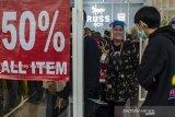 Pekerja menggunakan pelindung wajah saat memasukkan warga untuk berbelanja pakaian di kawasan Pusat Distributor Outlet (Distro) di Kota Bandung, Jawa Barat, Jumat (22/5/2020). Sejumlah Distro di Kota Bandung menerapkan antrean dan bergantian masuk guna memenuhi kebutuhan masyarakat khususnya remaja dalam berbelanja pakaian Lebaran saat masa PSBB pandemi COVID-19. ANTARA JABAR/Novrian Arbi/agr