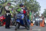 Petugas gabungan memeriksa surat keterangan pengendara roda dua saat pemeriksaan kendaraan pemudik di Perbatasan Karawang-Bekasi, Jawa Barat, Jumat  (22/5/2020). Pemeriksaan tersebut sebagai antisipasi pemudik yang akan melintasi jalur Pantura Karawang. ANTARA JABAR/M Ibnu Chazar/agr
