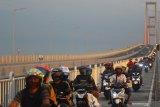 Pengendara motor melintas di Jembatan Suramadu, Surabaya, Jawa Timur, Jumat (22/5/2020). Pada H-2 Hari Raya Idul Fitri 1441 H, jembatan yang menjadi penghubung antara Pulau Jawa dan Pulau Madura tersebut mulai dipadati kendaraan terutama kendaraan roda dua yang mudik menuju Pulau Madura di tengah pandemi COVID-19. Antara Jatim/Moch Asim/zk.