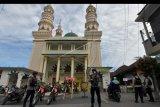 Anggota Brimob Polda Bali memantau situasi menjelang malam perayaan Idul Fitri di kawasan Masjid Al-Muhajirin Kepaon, Denpasar, Bali, Sabtu (23/5/2020). Kegiatan tersebut untuk memantau aktrivitas masyarakat agar tidak berkumpul atau berkerumun pada perayaan Hari Raya Idul Fitri 1441 H terkait penerapan pembatasan kegiatan masyarakat (PKM) kota Denpasar dalam upaya menghentikan penyebaran COVID-19. ANTARA FOTO/Nyoman Hendra Wibowo/nym.