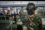 Personel TNI menggunakan helm pendeteksi suhu tubuh di Terminal 3 Bandara Internasional Soekarno Hatta, Tangerang, Banten, Sabtu (23/5/2020). Helm thermal KC wearable tersebut digunakan sebagai alat pendeteksi suhu tubuh hingga jarak 10 meter. ANTARA FOTO/Fauzan/nym.