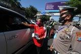 Petugas memeriksa suhu tubuh dan KTP pengendara mobil berplat nomor luar daerah di Kota Kediri, Jawa Timur, Sabtu (23/5/2020). Menjelang lebaran polisi memperketat akses masuk di perbatasan Kota Kediri untuk meminimalisir pemudik sebagai upaya menangkal penyebaran COVID-19. Antara Jatim/Prasetia Fauzani/zk