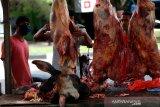 Pedagang musiman memotong daging sapi yang dijajakan untuk kebutuhan perayaan hari tradisi pemotongan hewan ternak (meugang) di Aceh, Besar, Aceh, Sabtu (23/5/2020). Harga daging untuk kebutuhan meugang yang dirayakan tiga kali dalam setahun oleh masyarakat di provinsi Aceh dijual Rp140.000 hingga Rp170.000 per kilogram tergantung jenis sapi atau kerbau. Antara Aceh/Irwansyah Putra.