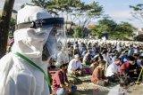 Seorang Panitia menggunakan APD lengkap saat memantau kondisi warga dalam pelaksanaan Shalat Id di Baleendah, Kabupaten Bandung, Jawa Barat, Minggu (24/5/2020). Warga di kawasan tersebut melaksanakan Shalat Idul Fitri 2020 dengan menerapkan protokol kesehatan seperti penggunaan masker, sarung tangan, disemprot disinfektan serta pemberian batas dan jarak guna mengurangi resiko terpapar virus COVID-19. ANTARA JABAR/Novrian Arbi/agr