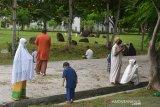Warga berdoa di kuburan masal Tsunami Desa Ulee Lheue, Banda Aceh, Aceh, Minggu (24/5/2020). Seusai melaksanakan Shalat Idul Fitri, warga di daerah itu ramai melakukan ziarah di Kuburan Tsunami dan selain Tempat Pemakaman Umum guna mendoakan keluarga dan kerabatnya yang telah wafat. Antara Aceh/Ampelsa.
