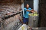 Warga memasak ketupat di industri rumahan pembuatan ketupat dan lepet di Desa Ngumpul, Kecamatan Jogoroto, Kabupaten Jombang, Jawa Timur, Selasa (26/5/2020). Ketupat dan lepet matang tersebut selanjutnya dijual dengan harga Rp11 ribu per sepuluh biji. Antara Jatim/Syaiful Arif/zk