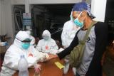 Petugas Dinas Kesehatan Provinsi Kalbar melakukan tes diagnostik cepat atau rapid test COVID-19 pekerja Migran Indonesia (PMI) dari Malaysia di Kantor Dinas Sosial Provinsi Kalbar di Pontianak, Selasa (26/5/2020) malam. Badan Perlindungan Pekerja Migran Indonesia (BP2MI) mencatat terdapat 179 PMI bermasalah yang dipulangkan Pemerintah Malaysia melalui Pos Lintas Batas Negara (PLBN) Entikong Kalbar karena tidak memiliki paspor dan izin kerja. ANTARA FOTO/Jessica Helena Wuysang/aww.
