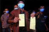 Dua Pekerja Migran Indonesia (PMI) dari Malaysia memperlihatkan kartu kewaspadaan kesehatan atau Health Alert Card (HAC) sebelum menjalani tes diagnostik cepat atau rapid test COVID-19 setibanya mereka di Kantor Dinas Sosial Provinsi Kalbar di Pontianak, Selasa (26/5/2020) malam. Badan Perlindungan Pekerja Migran Indonesia (BP2MI) mencatat terdapat 179 PMI bermasalah yang dipulangkan Pemerintah Malaysia melalui Pos Lintas Batas Negara (PLBN) Entikong Kalbar karena tidak memiliki paspor dan izin kerja. ANTARA FOTO/Jessica Helena Wuysang/aww.
