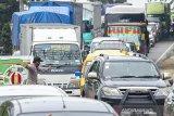 Petugas gabungan mengatur arus lalu lintas saat penyekatan arus balik menuju Jabodetabek di titik penyekatan perbatasan Karawang-Bekasi, Jawa Barat, Kamis (28/5/2020). Penyekatan arus balik tersebut untuk memeriksa pemudik yang akan menuju Jabodetabek guna memutus mata rantai penyebaran COVID-19. ANTARA JABAR/M Ibnu Chazar/agr