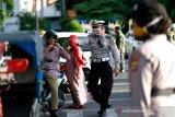 Personil Polresta Banda Aceh mengarahkan warga yang terjaring razia penggunaan masker yang dilakukan tim gabungan Pemerintah Kota Banda Aceh di Banda Aceh, Aceh, Kamis (28/5/2020). Tim gugus tugas percepatan penanganan COVID-19 Kota Banda Aceh menjaring dan mendata puluhan warga yang tidak memakai masker. Antara Aceh/Irwansyah Putra.