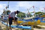 Nelayan memperbaiki perahunya di kawasan Pantai Kedonganan, Badung, Bali, Jumat (29/5/2020). Nelayan tradisional di kawasan tersebut memilih untuk tidak melaut akibat gelombang tinggi yang terjadi sejak tiga hari terakhir di perairan selatan Pulau Bali yang dapat membahayakan keselamatan nelayan. ANTARA FOTO/Fikri Yusuf/nym.