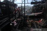 Sejumlah petugas pemadam kebakaran melakukan pendinginan di lokasi kebakaran rumah di kawasan Jalan Manggis, Banjarmasin, Kalimantan Selatan, Jumat (29/5/2020). Sebanyak empat rumah warga dan satu bedakan lima pintu hangus terbakar di kawasan permukiman padat penduduk tersebut, dimana penyebab kebakaran masih dalam penyelidikan kepolisian. Foto Antaranews Kalsel/Bayu Pratama S.