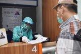 Petugas loket dengan menggunakan masker, pelindung wajah dan sarung tangan melayani konsumen di Stasiun Kereta Api (KA) Madiun, Jawa Timur, Sabtu (30/5/2020). PT KAI melakukan adaptasi persiapan pelaksanaan memasuki era normal baru antara lain dengan penggunaan masker, pelindung wajah, pemeriksaan suhu tubuh dan jaga jarak di tengah masa pandemi guna pencegahan penyebaran COVID-19. Antara Jatim/Siswowidodo/zk