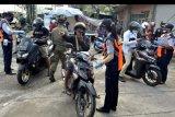 Petugas memeriksa tujuan dan keperluan warga yang memasuki wilayah Denpasar di kawasan Uma Anyar, Denpasar, Bali, Minggu (31/5/2020). Pemeriksaan tersebut dilakukan untuk mengawasi dan membatasi masyarakat yang akan memasuki wilayah Kota Denpasar selama masa penerapan Pembatasan Kegiatan Masyarakat (PKM) di Denpasar serta arus balik Lebaran 2020 sebagai upaya untuk mencegah penyebaran COVID-19. ANTARA FOTO/Fikri Yusuf/nym