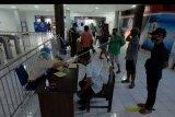 Petugas kesehatan memeriksa suhu tubuh sopir truk pengangkut barang yang datang dari pulau Jawa setibanya mereka di Pelabuhan Gilimanuk, Jembrana, Bali, Minggu (31/5/2020). Provinsi Bali memperketat keluar masuknya orang melalui pelabuhan laut dan udara dengan sejumlah persyaratan yang di nataranya surat izin jalan dan surat sehat / bebas COVID-19 untuk memutus wabah COVID-19 sehingga bisa segera mengikuti tatanan normal baru. ANTARA FOTO/Nyoman Hendra Wibowo/nym