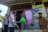 Direktur Polisi Air Polda Aceh, Kombes Pol Jemmy Rosdiantoro (kedua kiri) menyerahkan bantuan paket sembako kepada seorang  warga prasejahtera saat kunjungan di Desa Lapeng, Pemukiman Pulau Beras Utara, kecamatan Pulau Aceh, kabupaten Aceh Besar, Aceh, Senin (1/6/2020). Bantuan  paket sembako untuk 374 jiwa warga prasejahtera dan dilanjutkan sosialisasi penggunaan masker di wilayah terluar Pulau Aceh yang terdampak pandemi COVID-19  tersebut, merupakan rangkaian dari kegiatan bhakti sosial dalam rangka Peringatan Hari Lahir  Pancasila. Antara Aceh/Ampelsa.