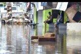 Warga berada di depan tempat tinggalnya saat banjir di kawasan Glogor Carik, Denpasar, Bali, Senin (1/6/2020). Hujan yang mengguyur wilayah Denpasar sejak Minggu (31/5) malam menyebabkan sejumlah titik di Denpasar tergenang air dengan ketinggian bervariasi. ANTARA FOTO/Fikri Yusuf/nym.