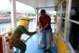 Pramugari kapal memberikan cairan handsanitizer pada penumpang KMP Dharma Rucita di Pelabuhan Ketapang, Banyuwangi, Jawa Timur, Senin (1/6/2020). Sebagian operator kapal penyeberangan pelabuhan ketapang-Gilimanuk mulai menerapkan tatanan normal baru. Antara Jatim/Budi Candra Setya/zk