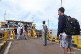 Petugas menggunakan baju hazmat memeriksa suhu penumpang KMP Dharma Rucita di Pelabuhan Ketapang, Banyuwangi, Jawa Timur, Senin (1/6/2020). Sebagian operator kapal penyeberangan pelabuhan ketapang-Gilimanuk mulai menerapkan tatanan normal baru. Antara Jatim/Budi Candra Setya/zk