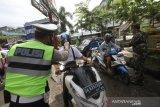 Anggota Polisi dan TNI melakukan pengecekan suhu tubuh kepada pengunjung Pasar Sentra Antasari di Banjarmasin, Kalimantan Selatan, Senin (1/6/2020). Pemerintah Kota Banjarmasin menghentikan pemberlakuan Pembatasan Sosial Berskala Besar (PSBB) pada Minggu (31/5/2020) dan memberlakukan Kondisi Tanggap Darurat COVID-19 Pasca PSBB serta memberikan edukasi protokol kesehatan yang merupakan tahapan menuju normal baru (New Normal) kepada masyarakat. Foto Antaranews Kalsel/Bayu Pratama S.