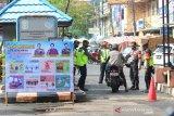 Anggota Polisi berjaga di pintu masuk Pasar Sudimampir di Banjarmasin, Kalimantan Selatan, Senin (1/6/2020). Pemerintah Kota Banjarmasin menghentikan pemberlakuan Pembatasan Sosial Berskala Besar (PSBB) pada Minggu (31/5/2020) dan memberlakukan Kondisi Tanggap Darurat COVID-19 Pasca PSBB serta memberikan edukasi protokol kesehatan yang merupakan tahapan menuju normal baru (New Normal) kepada masyarakat. Foto Antaranews Kalsel/Bayu Pratama S.