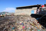 Warga melihat nelayan beraktivitas diantara sampah yang menumpuk di pesisir pantai Muncar , Banyuwangi, Jawa Timur, Selasa (2/6/2020). Sampah yang menumpuk dipesisir pantai akibat kurangnya kesadaran masyarakat yang membuang sembarangan itu, menyebabkan permasalahan pencemaran lingkungan menjadi kumuh. Antara Jatim/Budi Candra Setya/zk