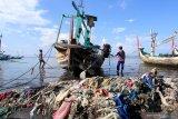 Nelayan beraktivitas diantara sampah yang menumpuk di pesisir pantai Muncar , Banyuwangi, Jawa Timur, Selasa (2/6/2020). Sampah yang menumpuk dipesisir pantai akibat kurangnya kesadaran masyarakat yang membuang sembarangan itu, menyebabkan permasalahan pencemaran lingkungan menjadi kumuh. Antara Jatim/Budi Candra Setya/zk