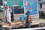 TNI lakukan penyemprotan  disinfektan rumah warga distrik Poom