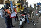 Petugas mendata pemudik dan kendaraan yang memasuki wilayah Badung dan Denpasar dalam operasi penyekatan arus balik Lebaran di Terminal Mengwi, Badung, Bali, Kamis (4/6/2020). Pemeriksaan dilakukan secara bertahap di sejumlah kawasan setelah adanya dugaan lolosnya para pendatang dari Jawa hingga ke kabupaten lain di Bali tanpa adanya kelengkapan surat keterangan terutama keterangan sehat / bebas COVID-19. ANTARA FOTO/Nyoman Hendra Wibowo/nym