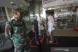 Anggota TNI berjaga di pintu masuk Q-Mall, Banjarbaru, Kalimantan Selatan, Jumat (5/6/2020). Pengelola pusat perbelanjaan tersebut menerapkan protokol kesehatan secara ketat berupa kewajiban mencuci tangan, pemeriksaan suhu tubuh, penggunaan masker, dan menyediakan fasilitas pendukung jaga jarak fisik (pshycal distancing) bagi pengunjung maupun karyawan guna mendukung pemerintah disaat kehidupan normal baru (New Normal). Foto Antaranews Kalsel/Bayu Pratama S.