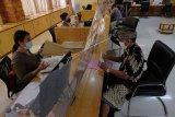 Pegawai Dinas Penanaman Modal dan Pelayanan Terpadu Satu Pintu Kota Denpasar melayani warga di Mal Pelayanan Publik Graha Sewaka Dharma, Denpasar, Bali, Jumat (5/6/2020). Aparatur Sipil Negara (ASN) di lingkungan Pemprov Bali mulai dipekerjakan kembali dalam tahapan-tahapan normal baru terhitung 5 Juni 2020 dengan mengikuti protokol kesehatan untuk mencegah kasus baru COVID-19. ANTARA FOTO/Nyoman Hendra Wibowo/nym.