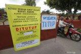Warga melintas di gerbang utama menuju kawasan wisata gunung Kelud di Kediri, Jawa Timur, Minggu (7/6/2020). Menjelang diberlakukaknya fase normal baru di tengah pandemi COVID-19 wisata andalan Kediri tersebut masih ditutup untuk umum hingga batas waktu yang belum ditentukan. Antara Jatim/Prasetia Fauzani/zk.
