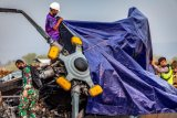 Petugas gabungan menutup bangkai helikopter yang jatuh menggunakan terpal di Kawasan Industri Kendal (KIK), Kabupaten Kendal, Jawa Tengah, Sabtu (6/6/2020). Belum diketahui penyebab jatuhnya helikopter jenis MI-17 bernomor registrasi HA 5141 milik TNI-AD yang mengakibatkan empat awak tewas dan lima awak lainnya dilarikan ke rumah sakit. ANTARA FOTO/Aji Styawan/WSJ.