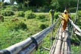 Dua orang guru SMA Negeri 1 Kabila melintasi jembatan bambu untuk mengantarkan soal ujian semester secara luar jaringan (luring) ke rumah murid di Poowo Barat, Kabupaten Bone Bolango, Gorontalo, Selasa (9/6/2020). Soal ujian tersebut diantar ke rumah 51 murid yang tidak memiliki telepon pintar (smartphone) untuk mengikuti ujian dalam jaringan (daring). ANTARA FOTO/Adiwinata Solihin/wsj.