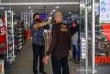 Petugas lakukan pengukuran suhu tubuh pengunjung pusat perbelanjaan di Palu