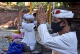 Umat Hindu melakukan persembahyangan Hari Tumpek Wayang dengan mengikuti protokol kesehatan di Pura Dalem Kahyangan Badung, Denpasar, Bali, Sabtu (13/6/2020). Persembahyangan tersebut untuk memohon agar wabah COVID-19 cepat berakhir menyusul adanya peningkatan kasus penularan secara transmisi lokal di Bali. ANTARA FOTO/Nyoman Hendra Wibowo/nym.