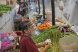 Pedagang beraktivitas dengan mengenakan masker dan pelindung wajah (face shield) di dalam kompleks pasar tradisional Bendorejo, Trenggalek, Jawa Timur, Sabtu (13/6/2020). Protokol kesehatan dalam rangka normal baru diterapkan ketat di pasar tradisional ini dengan memasang sekat transparan berbahan plastik untuk membatasi kontak langsung antara pedagang dengan pembeli, pemakaian pelindung wajah (face shield) bagi setiap pedagang, pemakaian masker, pengukuran suhu tubuh saat pembeli masuk kompleks pasar, hingga manajemen pengunjung guna mencegah kerumunan di dalam pasar. Antara Jatim/Destyan Sujarwoko/zk.