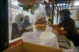Pembeli dan pedagang bertransaksi di dalam kompleks pasar tradisional Bendorejo, Trenggalek, Jawa Timur, Sabtu (13/6/2020). Protokol kesehatan dalam rangka normal baru diterapkan ketat di pasar tradisional ini dengan memasang sekat transparan berbahan plastik untuk membatasi kontak langsung antara pedagang dengan pembeli, pemakaian pelindung wajah (face shield) bagi setiap pedagang, pemakaian masker, pengukuran suhu tubuh saat pembeli masuk kompleks pasar, hingga manajemen pengunjung guna mencegah kerumunan di dalam pasar. Antara Jatim/Destyan Sujarwoko/zk.