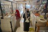 Pembeli dan pedagang beraktivitas dengan mengenakan masker di dalam kompleks pasar tradisional Bendorejo, Trenggalek, Jawa Timur, Sabtu (13/6/2020). Protokol kesehatan dalam rangka normal baru diterapkan ketat di pasar tradisional ini dengan memasang sekat transparan berbahan plastik untuk membatasi kontak langsung antara pedagang dengan pembeli, pemakaian pelindung wajah (face shield) bagi setiap pedagang, pemakaian masker, pengukuran suhu tubuh saat pembeli masuk kompleks pasar, hingga manajemen pengunjung guna mencegah kerumunan di dalam pasar. Antara Jatim/Destyan Sujarwoko/zk.