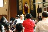 Petugas asisten imam membagikan Komuni Kudus kepada umat dengan tetap mengenakan masker dan face shield di Gereja Katolik Maria Ratu Damai Banyuwangi, Minggu (14/6/2020). Umat Katolik Banyuwangi kembali menggelar misa secara publik di gedung gereja dengan protokol kesehatan yang ketat, setelah 4 bulan misa digelar secara daring di rumah masing-masing karena pandemi COVID-19. Antara Jatim/Budi Candra Setya/zk.