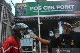 Petugas keamanan melakukan pengecekan suhu tubuh orang yang akan masuk ke kawasan Pondok Pesantren Tebuireng, Kabupaten Jombang, Jawa Timur, Selasa (16/6/2020). Pondok Pesantren Tebuireng dan Bahrul Ulum Tambakberas menjadi percontohan pesantren tangguh tanggap COVID-19 di Kabupaten Jombang untuk menghadapi era normal baru. Antara Jatim/Syaiful Arif/zk