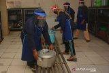Petugas dapur dengan menggenakan pelindung wajah memasak di dapur tangguh Pondok Pesantren Tebuireng, Kabupaten Jombang, Jawa Timur, Selasa (16/6/2020). Pondok Pesantren Tebuireng dan Bahrul Ulum Tambakberas menjadi percontohan pesantren tangguh tanggap COVID-19 di Kabupaten Jombang untuk menghadapi era normal baru. Antara Jatim/Syaiful Arif/zk
